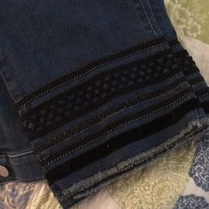 14. Ankle-length jeans with black detailing.